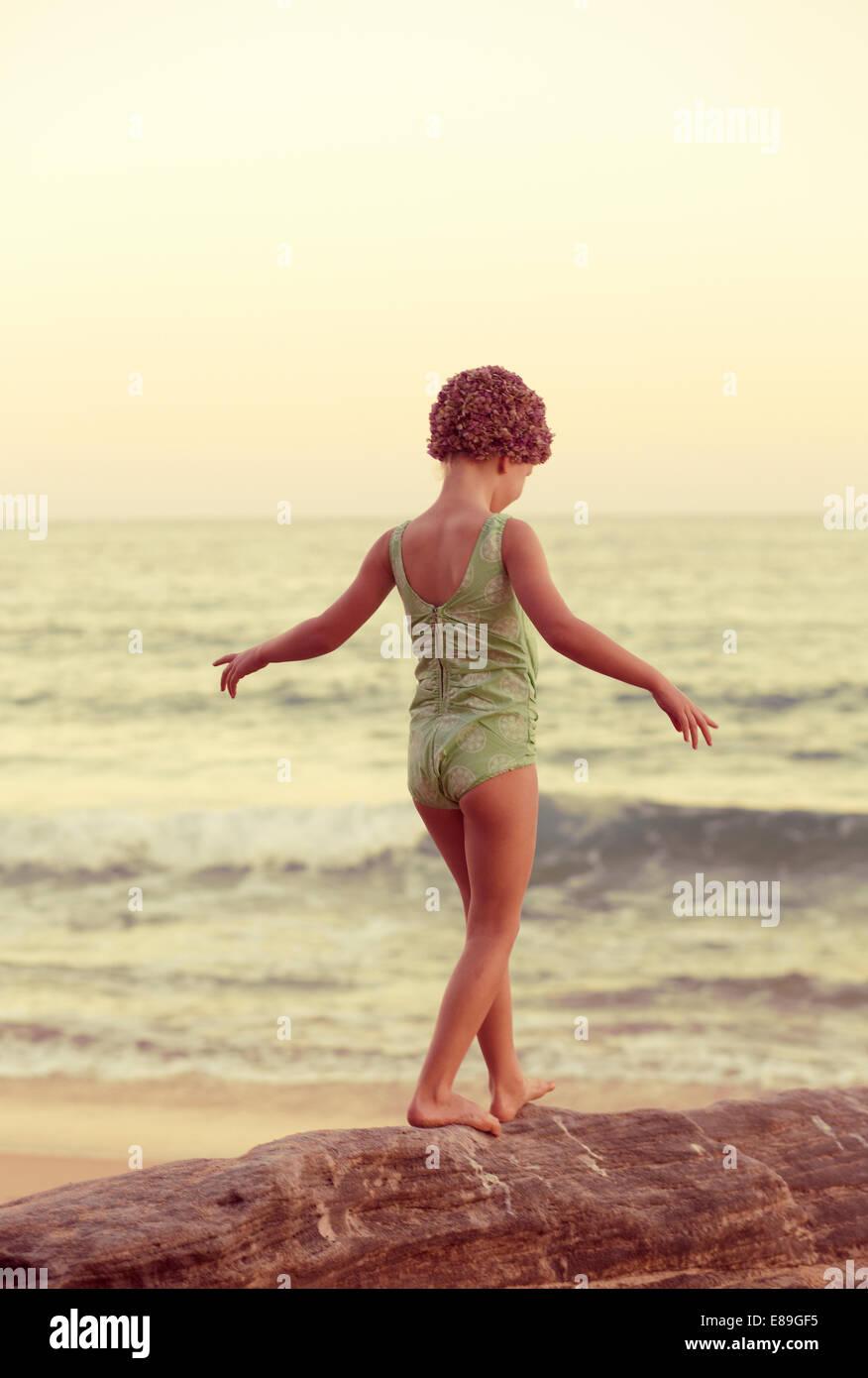 Mädchen in Oceanside Felsen entlang swimcap Stockbild