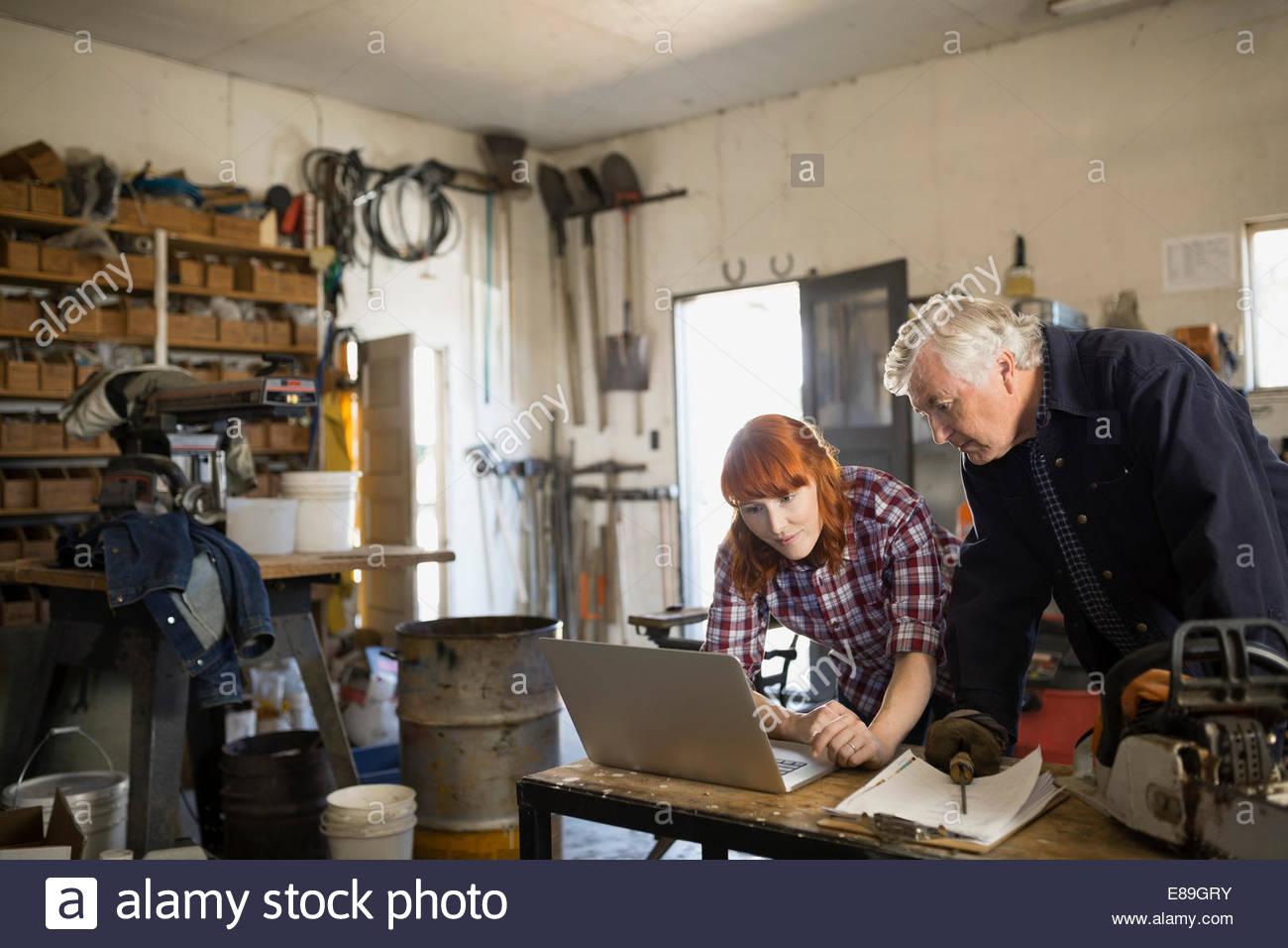 Vater und Tochter arbeiten am Laptop in Werkstatt Stockbild