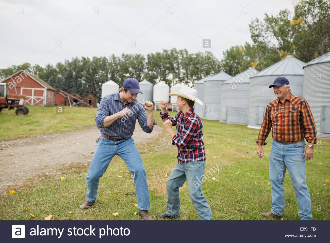 Vater und Sohn spielen kämpfen auf Bauernhof Stockbild