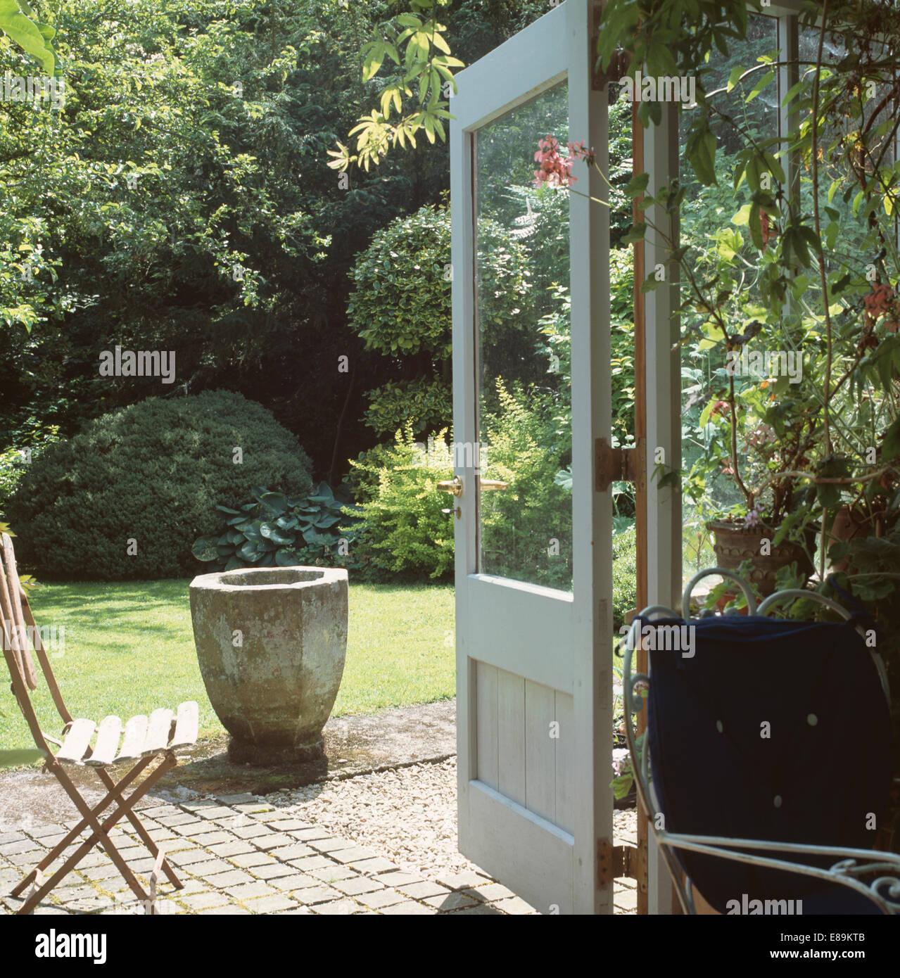 blick durch wintergarten fenstert ren zum garten mit stein. Black Bedroom Furniture Sets. Home Design Ideas