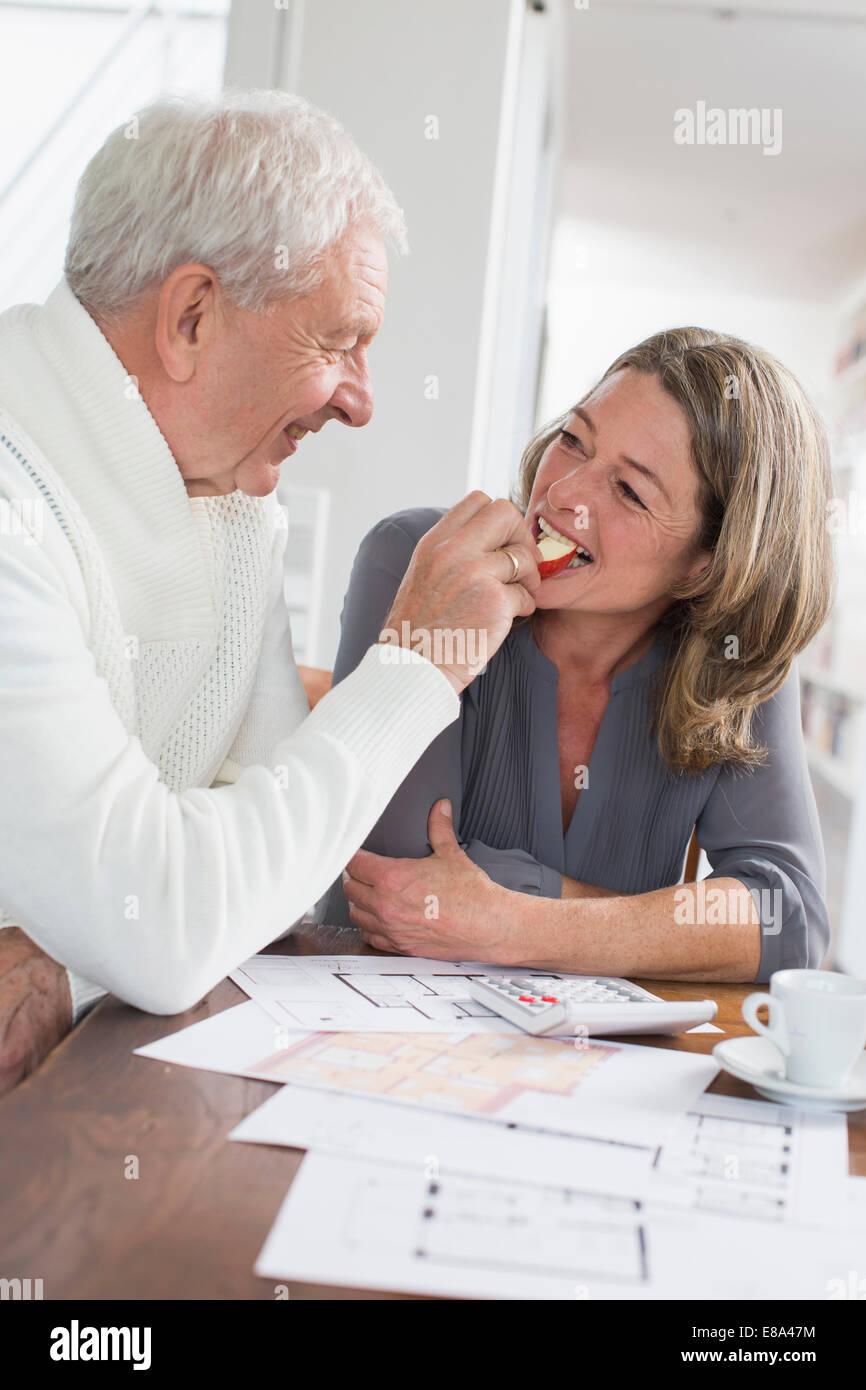 Happy senior woman Fütterung Frau mit Apfelscheiben Stockfoto
