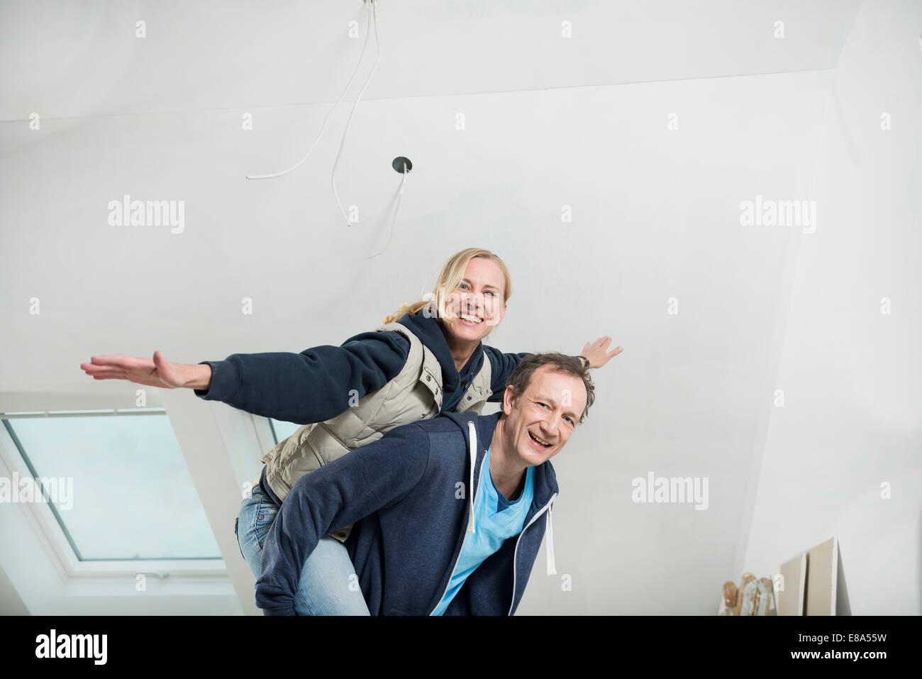 Mann seine Partnerin eine Huckepack während der Renovierung Stockbild
