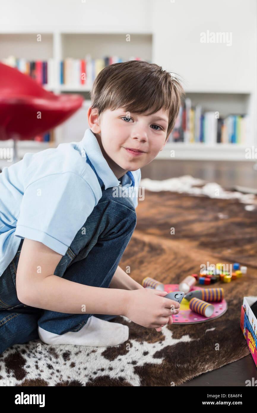 Porträt eines jungen spielen mit Brettspiel, Lächeln Stockbild