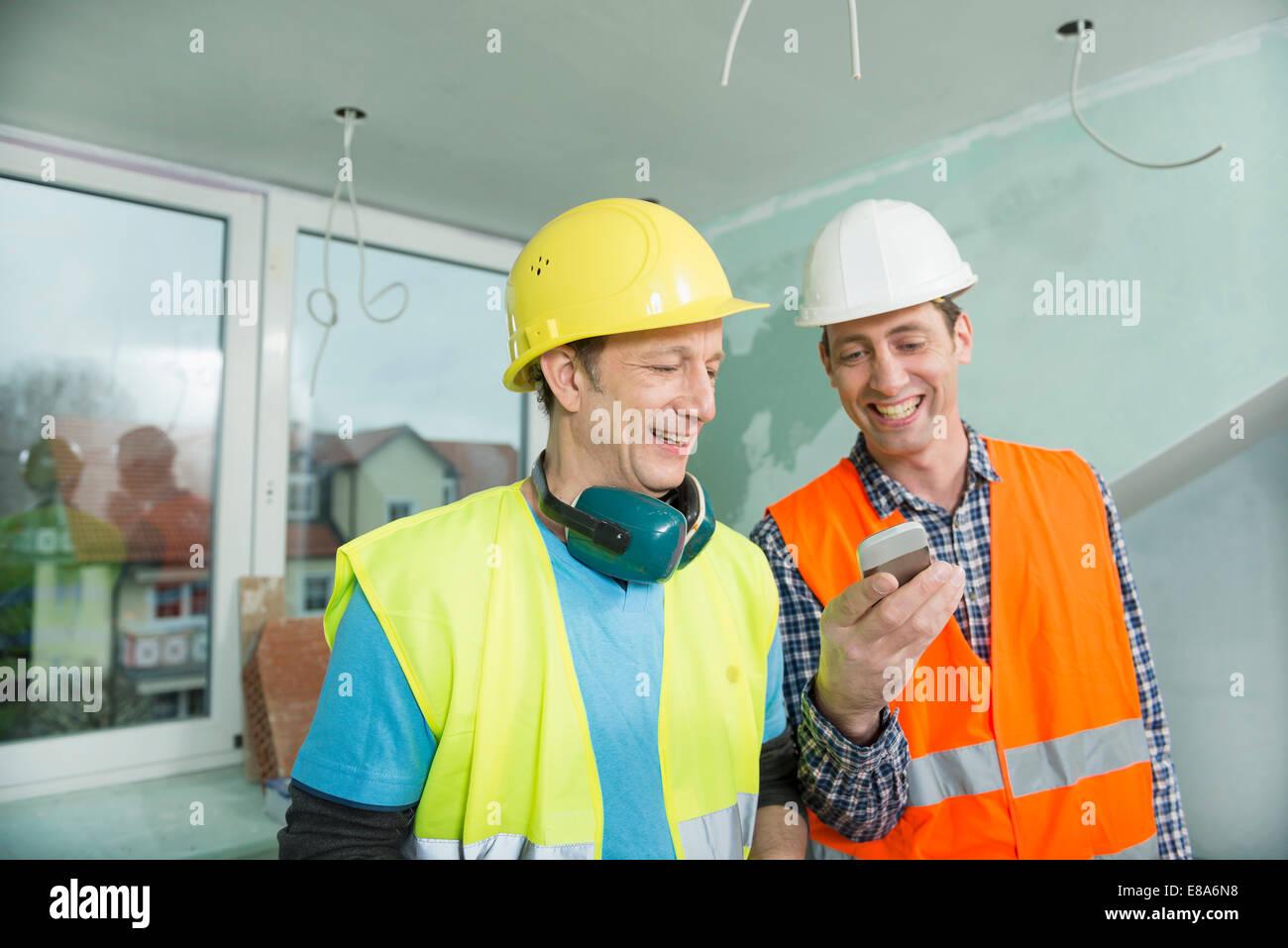 Zwei Bauarbeiter mit Smartphone auf Baustelle des Neubaus Stockbild