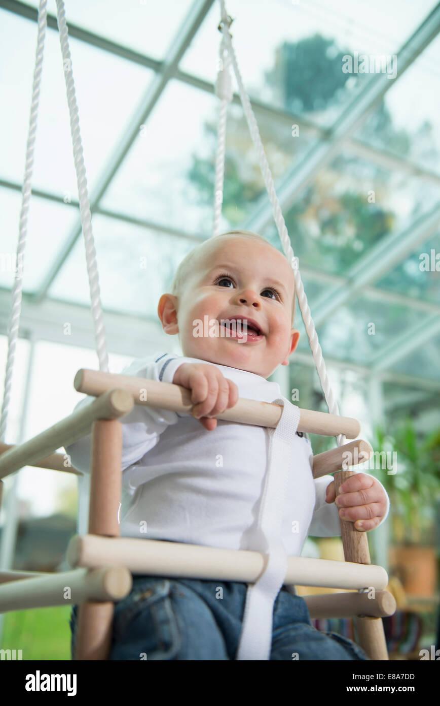 Porträt von lächelnden Kleinkind sitzt in einem Schwung Stockbild
