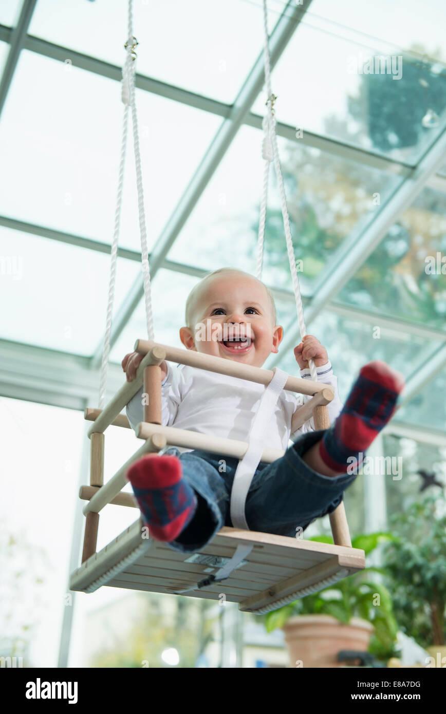 Porträt des lachenden Kleinkind sitzt in einem Schwung Stockbild