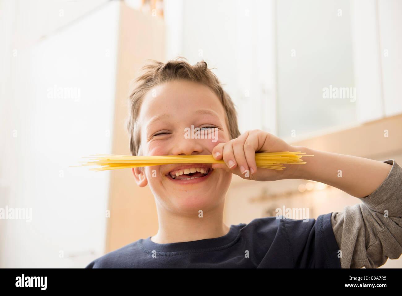 Lächelnde junge Spaghetti unter die Nase halten Stockbild