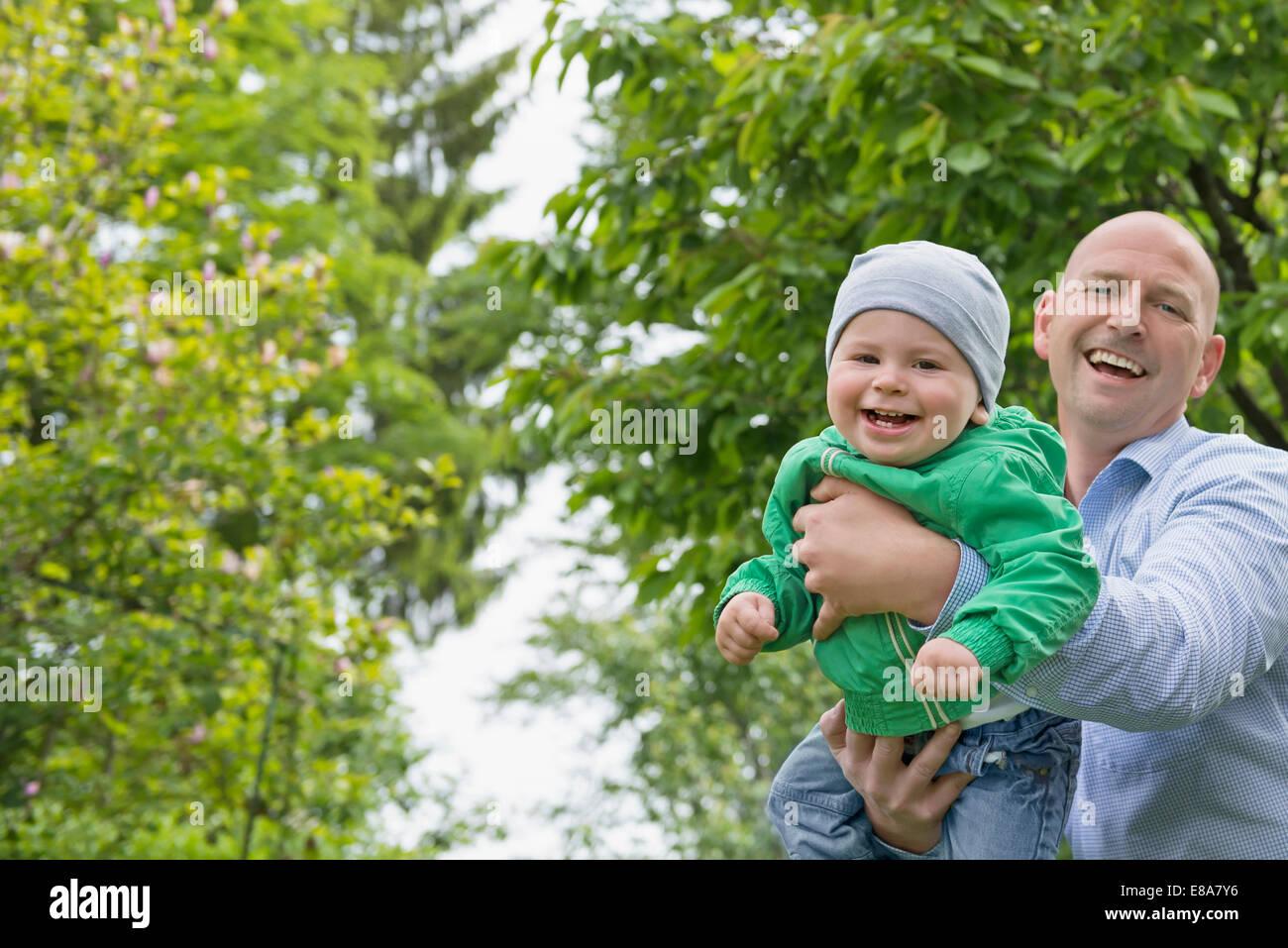 Vater hielt Babyjungen in Armen spielen fliegen Stockbild