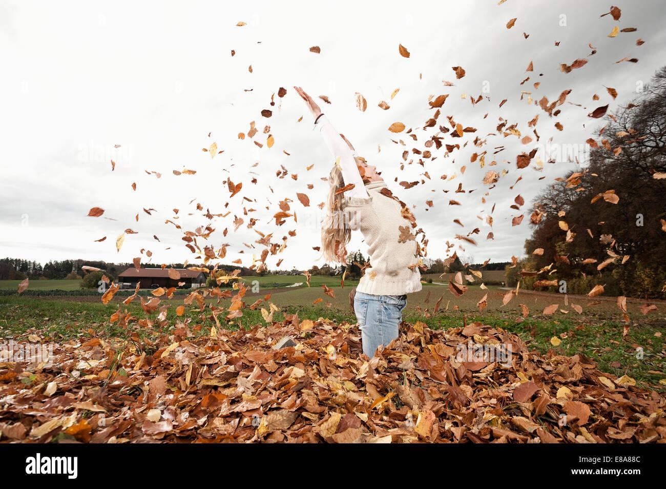 Glückliches Mädchen werfen Herbst Blätter Stockbild