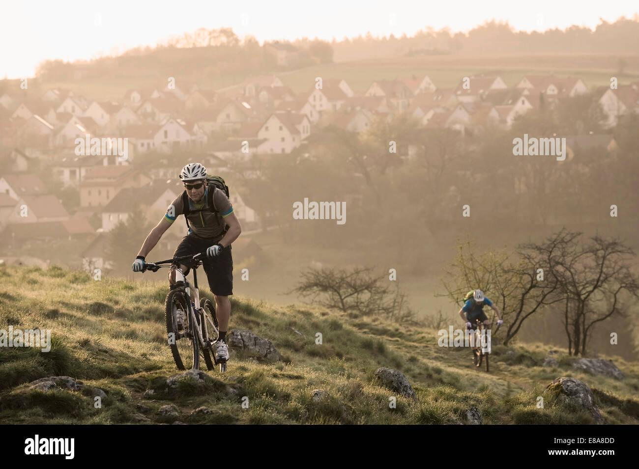 Junge Männer Mountainbiken bei Sonnenaufgang, Bayern, Germany Stockbild