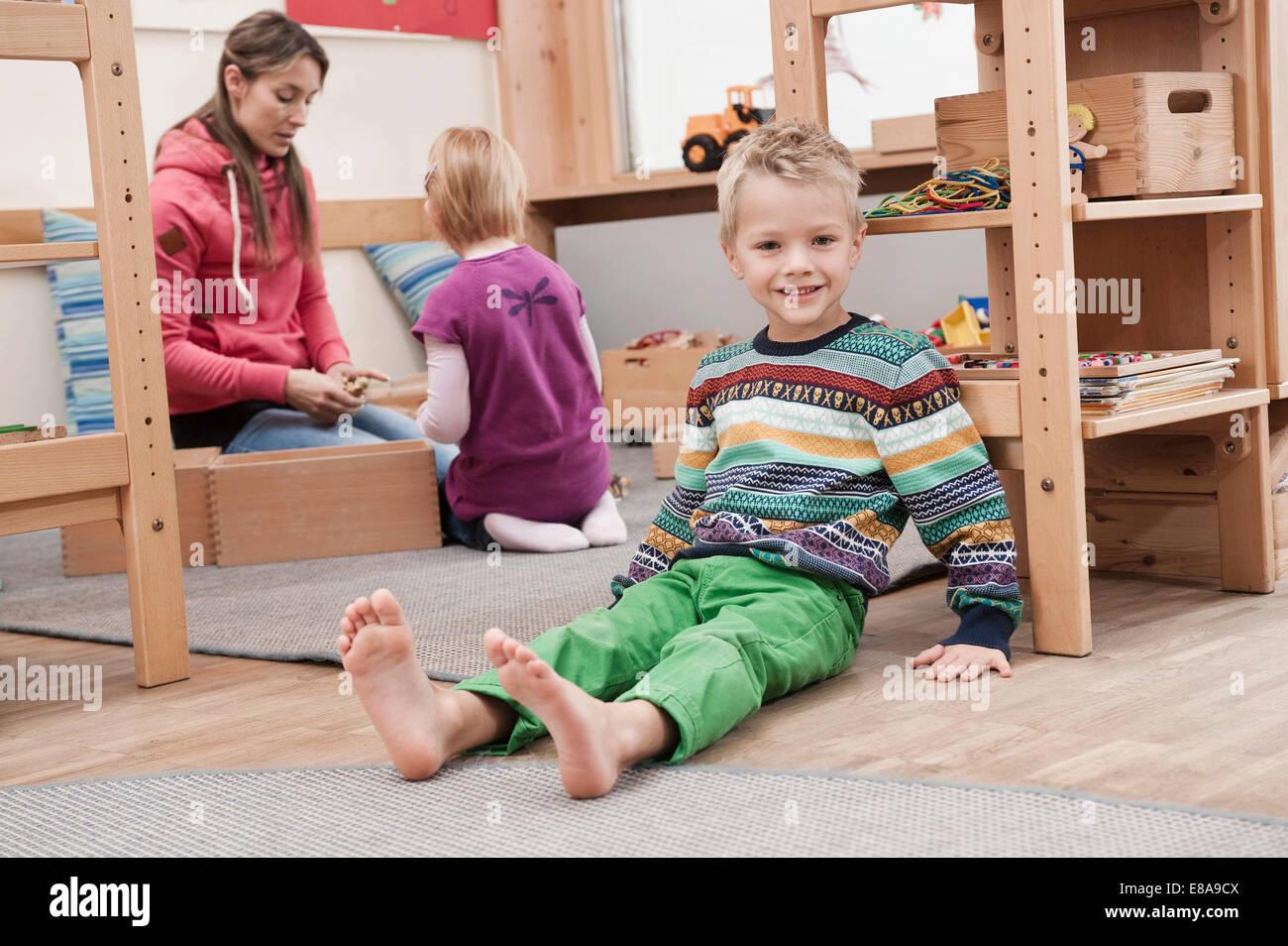 Kleiner Junge sitzt auf dem Boden in seinem kindergarten Stockbild