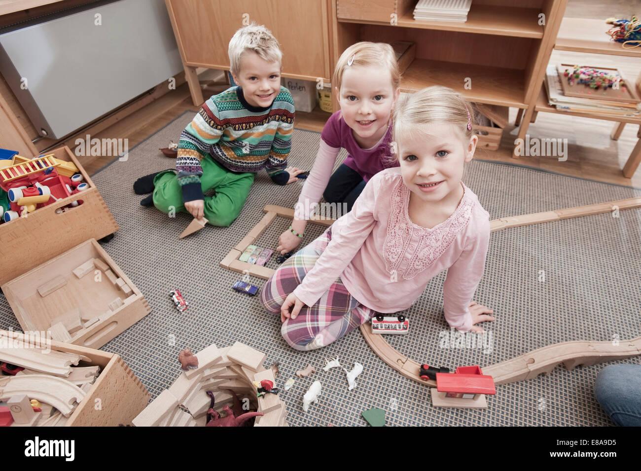 Drei kleine Kinder mit hölzernen Bausteine in ihrem kindergarten Stockbild