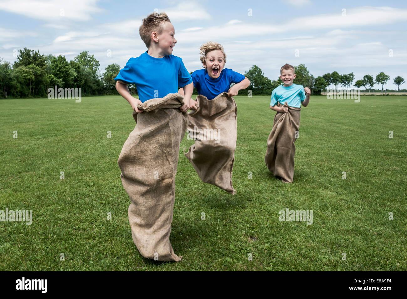 Drei junge Burschen läuft in Sackrace springen Stockbild