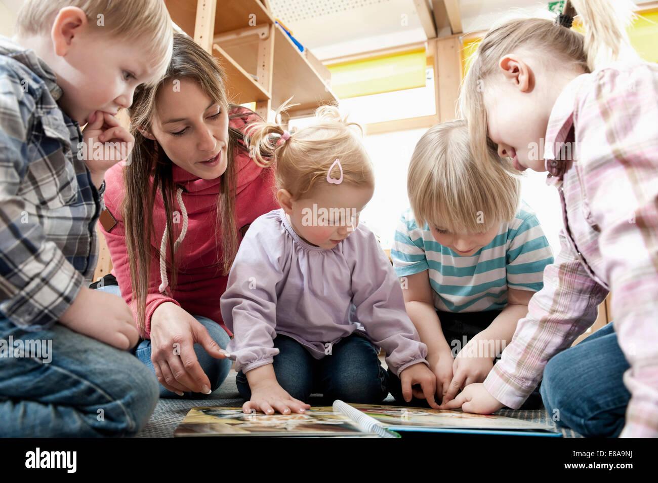 Weibliche Erzieher und vier Kinder Bilderbuch betrachten Stockbild