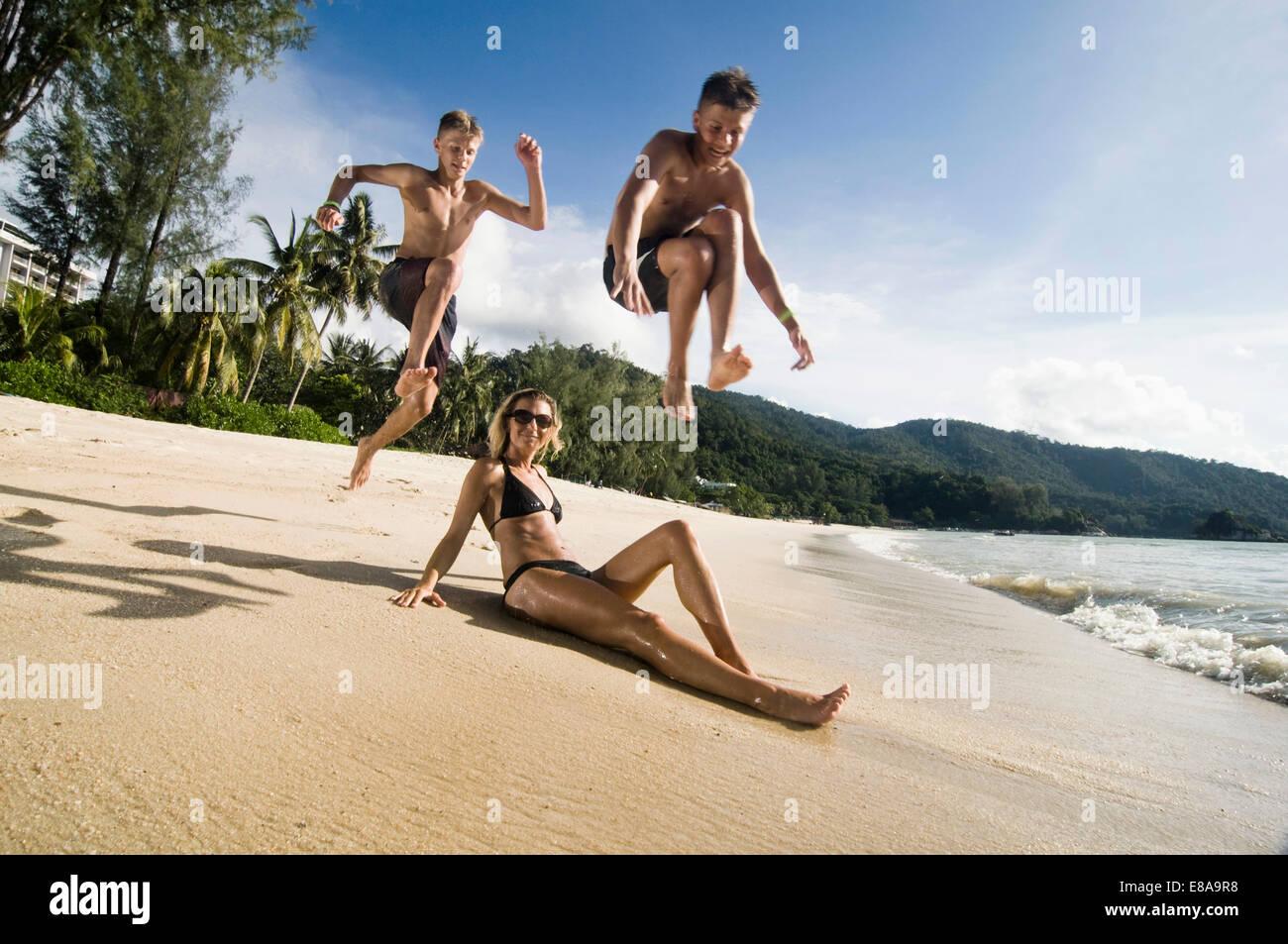 Mutter mit zwei halbwüchsigen Söhne am Strand, Penang, Malaysia Stockbild