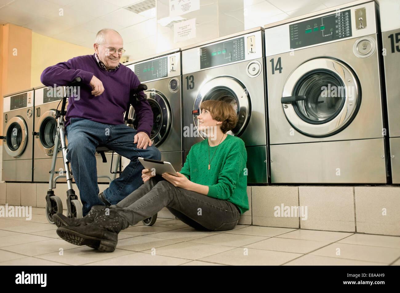 Mann und Frau sprechen in Wäscherei, Lächeln Stockbild