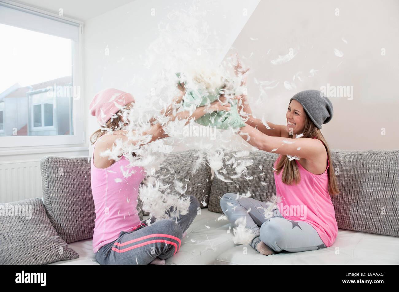 Zwei Freundinnen sitzen auf couch zu Hause haben Kissen Kampf Stockbild