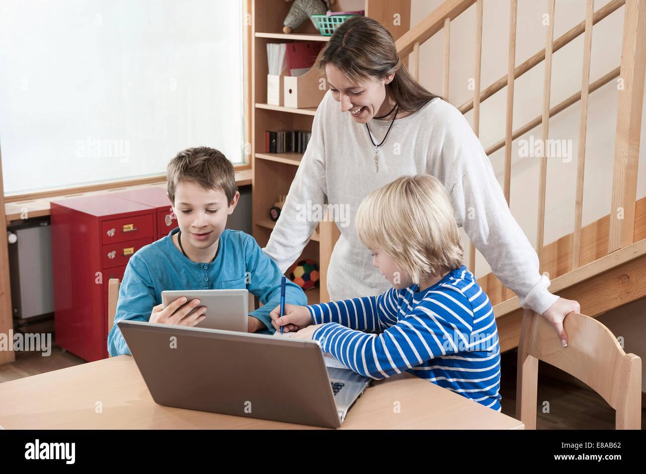 Zwei jungen und weiblichen Kinderpflegerin mit Laptop und Tablet-computer Stockbild