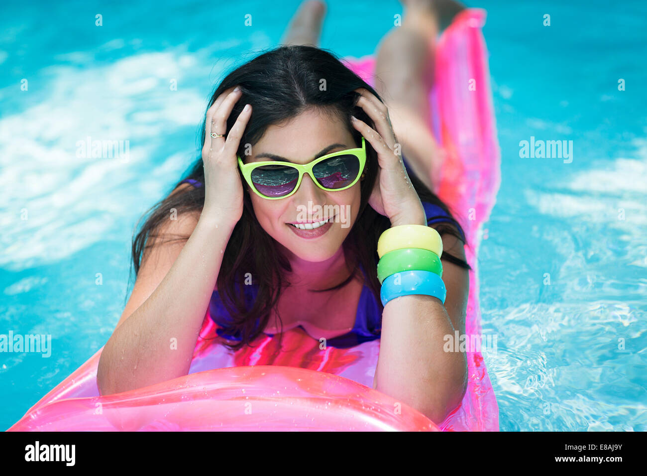 Porträt der jungen Frau auf Luftmatratze im Pool Sonnenbaden Stockbild