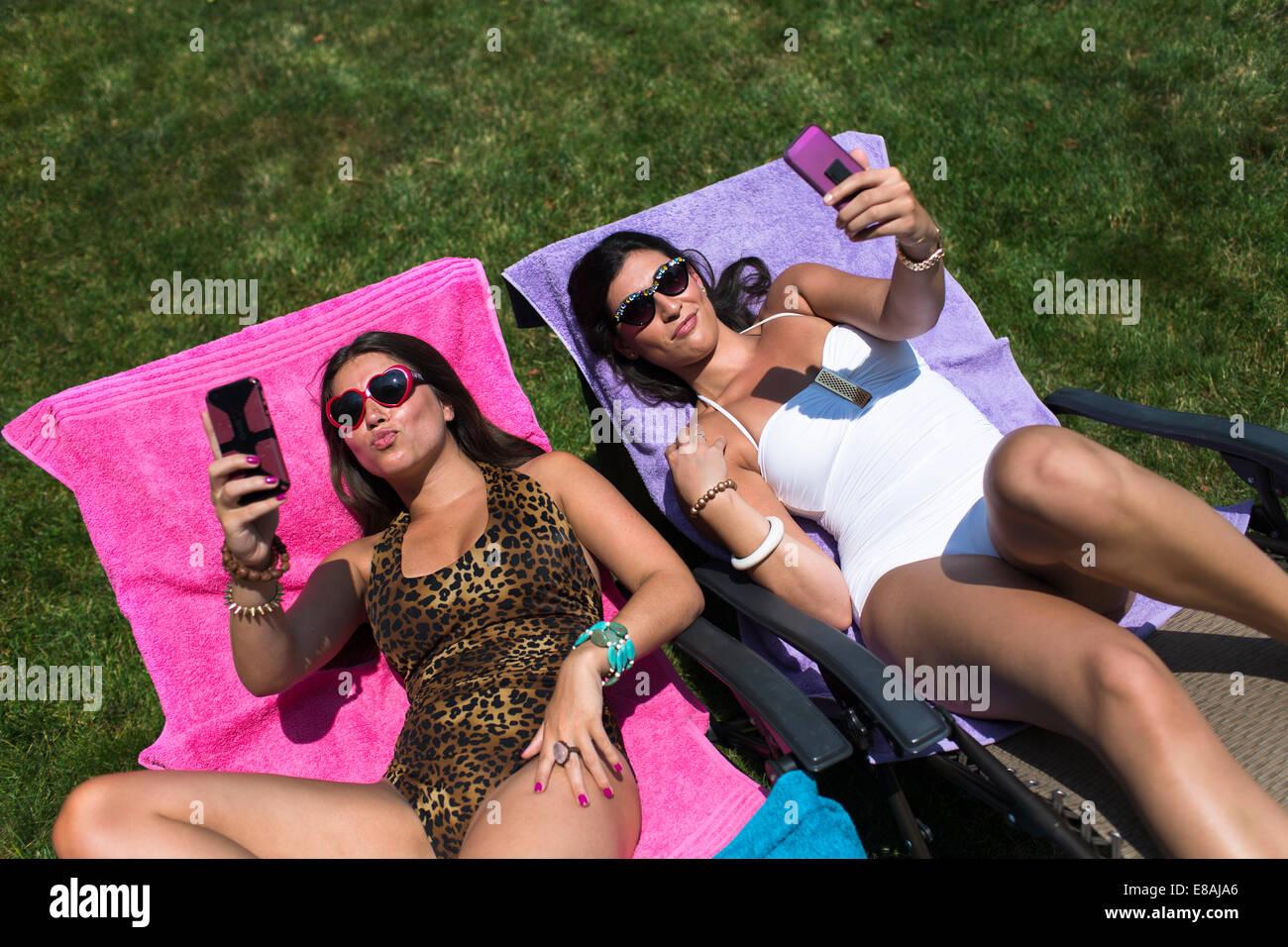 Zwei Schwestern, die unter Selfies, während auf Liegestühlen im Garten zum Sonnenbaden Stockbild