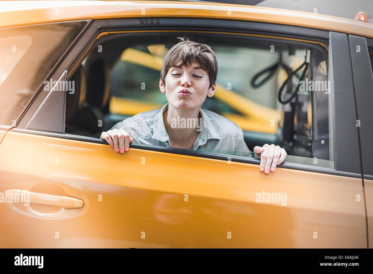 Frau bläst Kuss von gelbes Taxi, New York, USA Stockbild