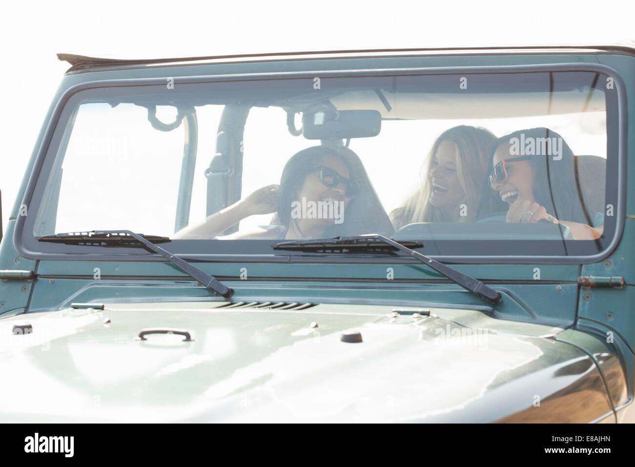 Drei junge Frauen lachen und plaudern im jeep Stockbild