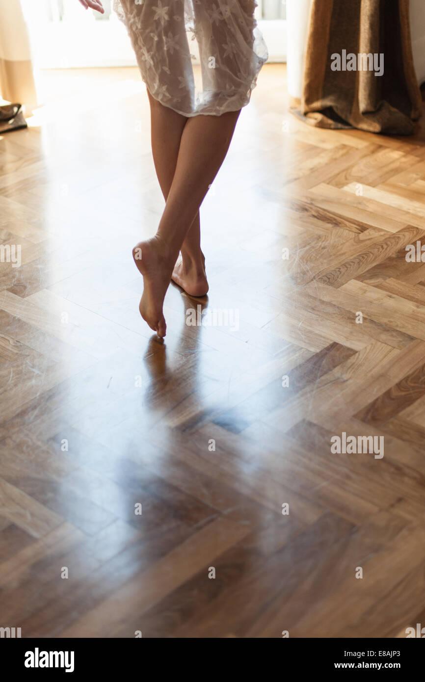 Beine und nackte Füße der jungen Frau auf Holzboden im Wohnzimmer Stockbild