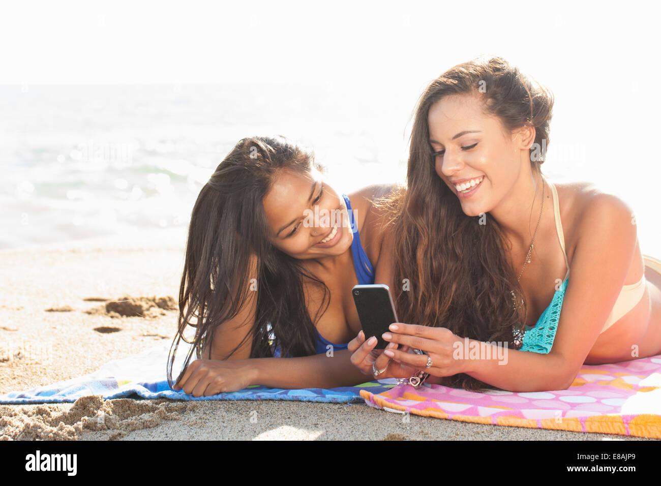 Zwei junge Frauen, Sonnenbaden und Blick auf Smartphone am Strand von Malibu, Kalifornien, USA Stockbild