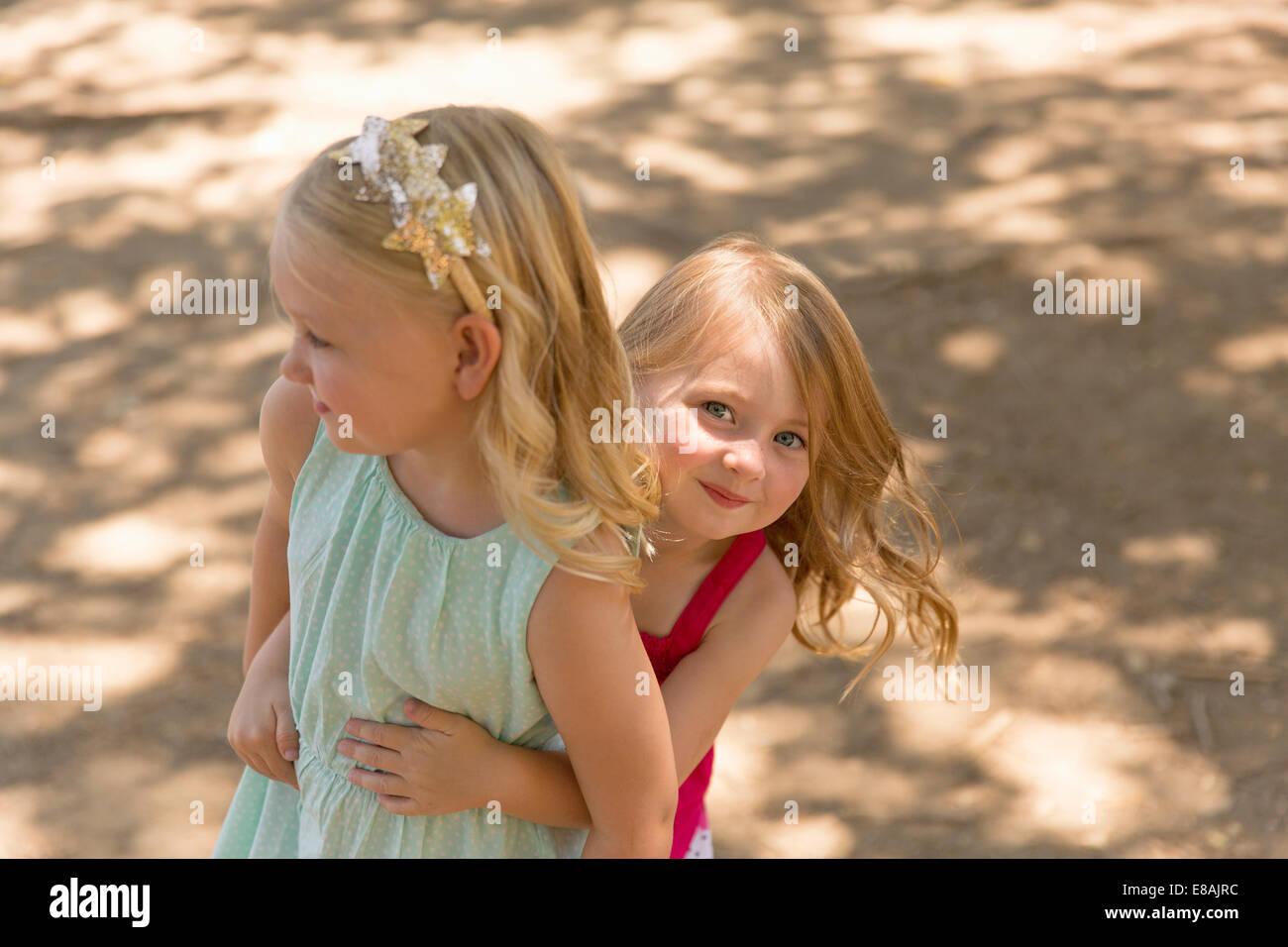 Junges Mädchen versteckt sich hinter Schwester im park Stockfoto