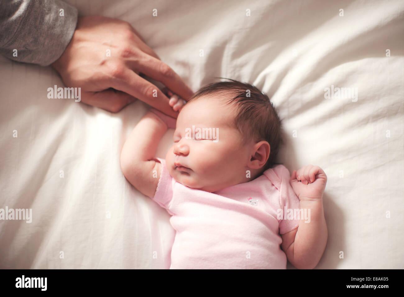 Babymädchen schläft, Hände von Vater Stockbild