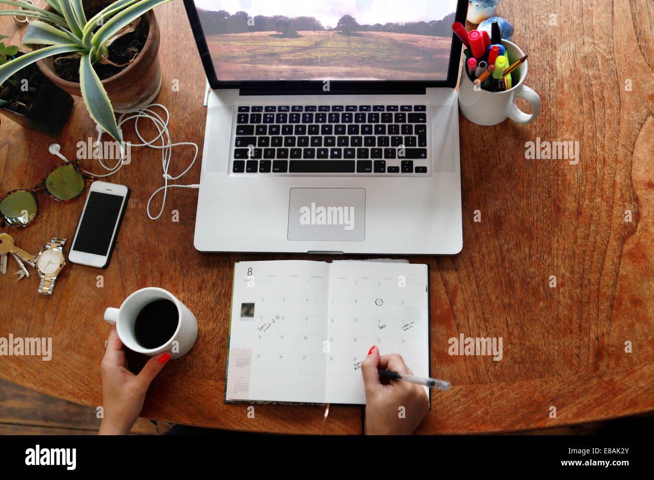 Person schriftlich Tagebuch mit Laptop am Schreibtisch Stockbild