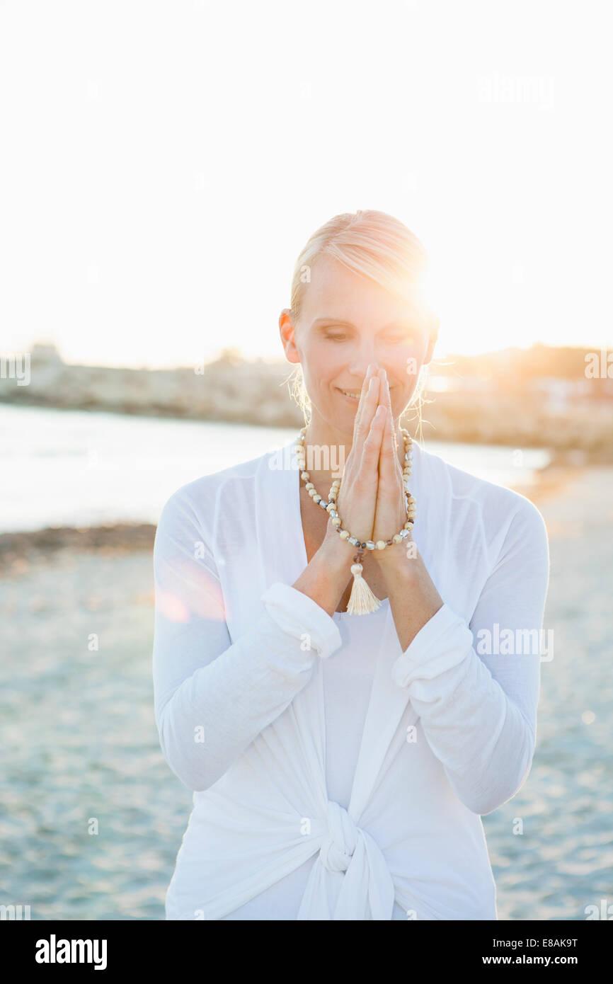 Frau in Yoga-Gebet-Pose am Strand Stockbild