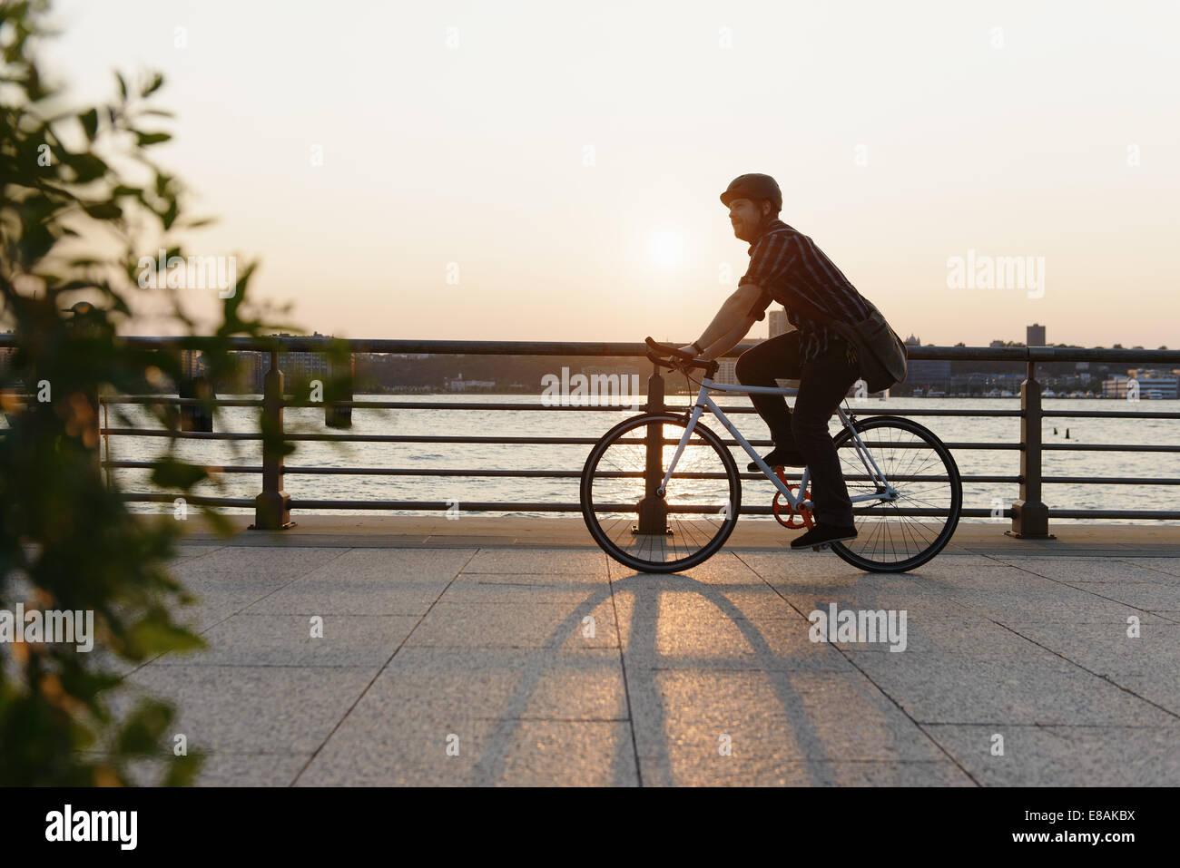 Männliche Messenger Radfahren entlang Stadt am Fluss Stockfoto