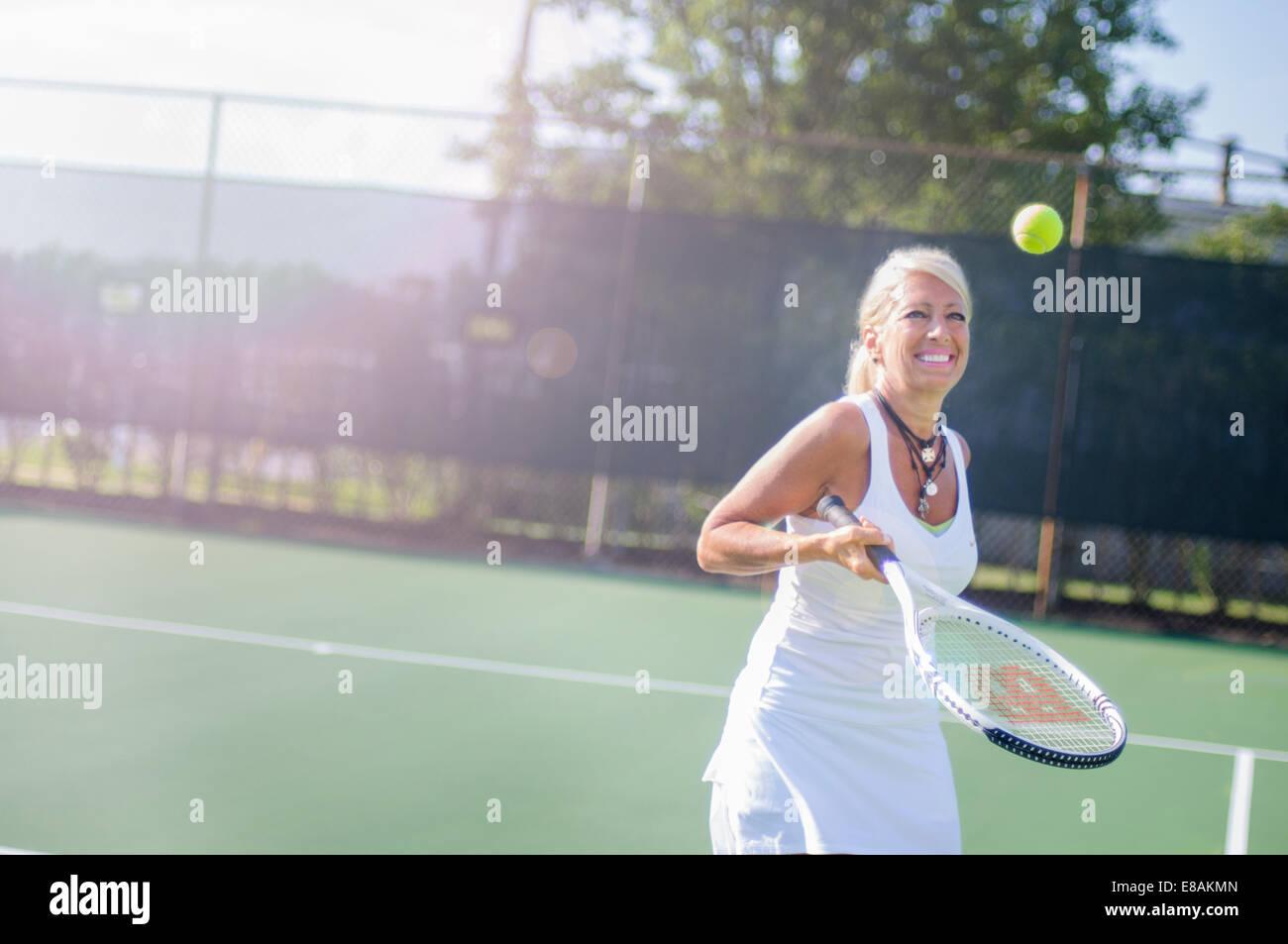 Reife Frau mit dem Tennisspielen lächelnd Stockbild