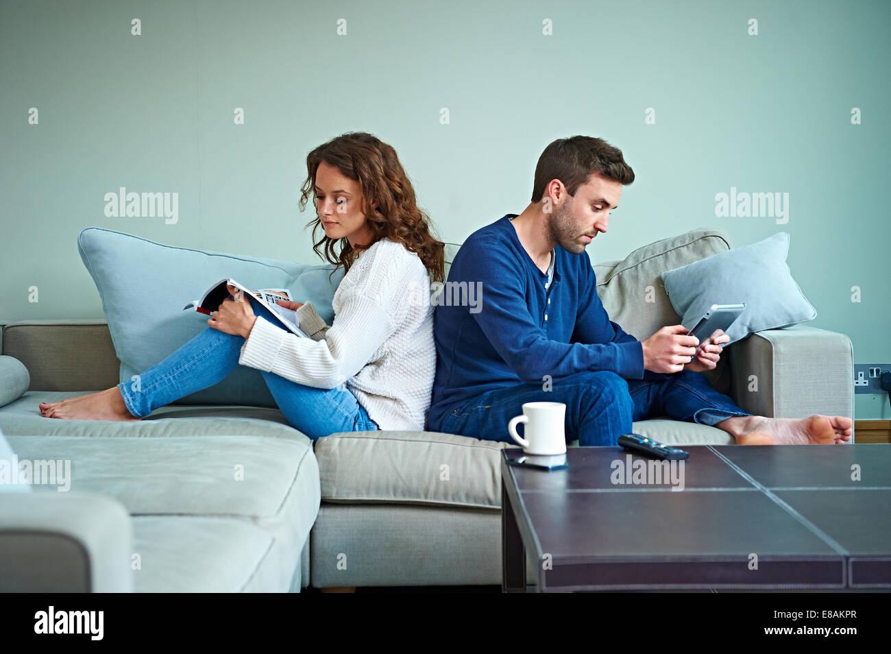 Paar auf Sofa lesen Stockbild