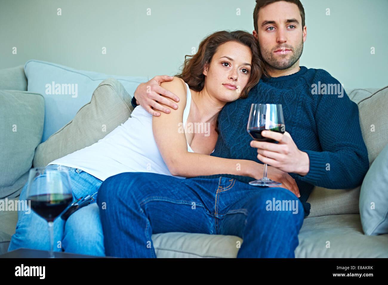 Paar genießen Wein auf sofa Stockbild
