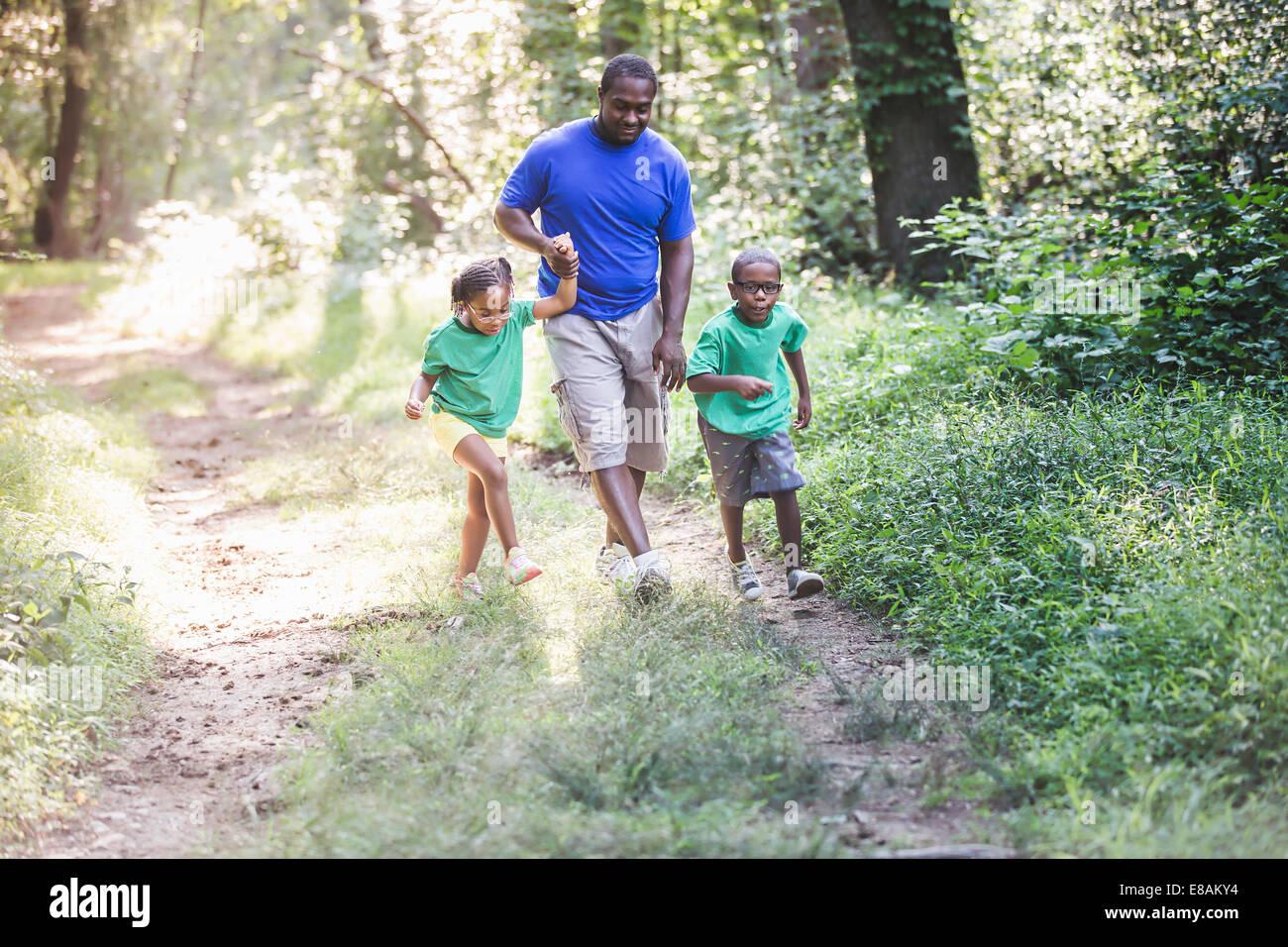 Vater zu Fuß durch Wald mit Tochter und Sohn im Eco camp Stockbild