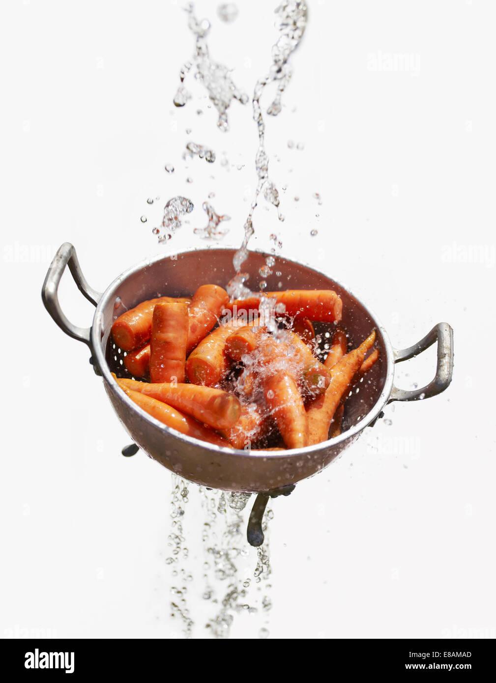 Wasser fällt durch das Sieb mit frischen Karotten Stockbild