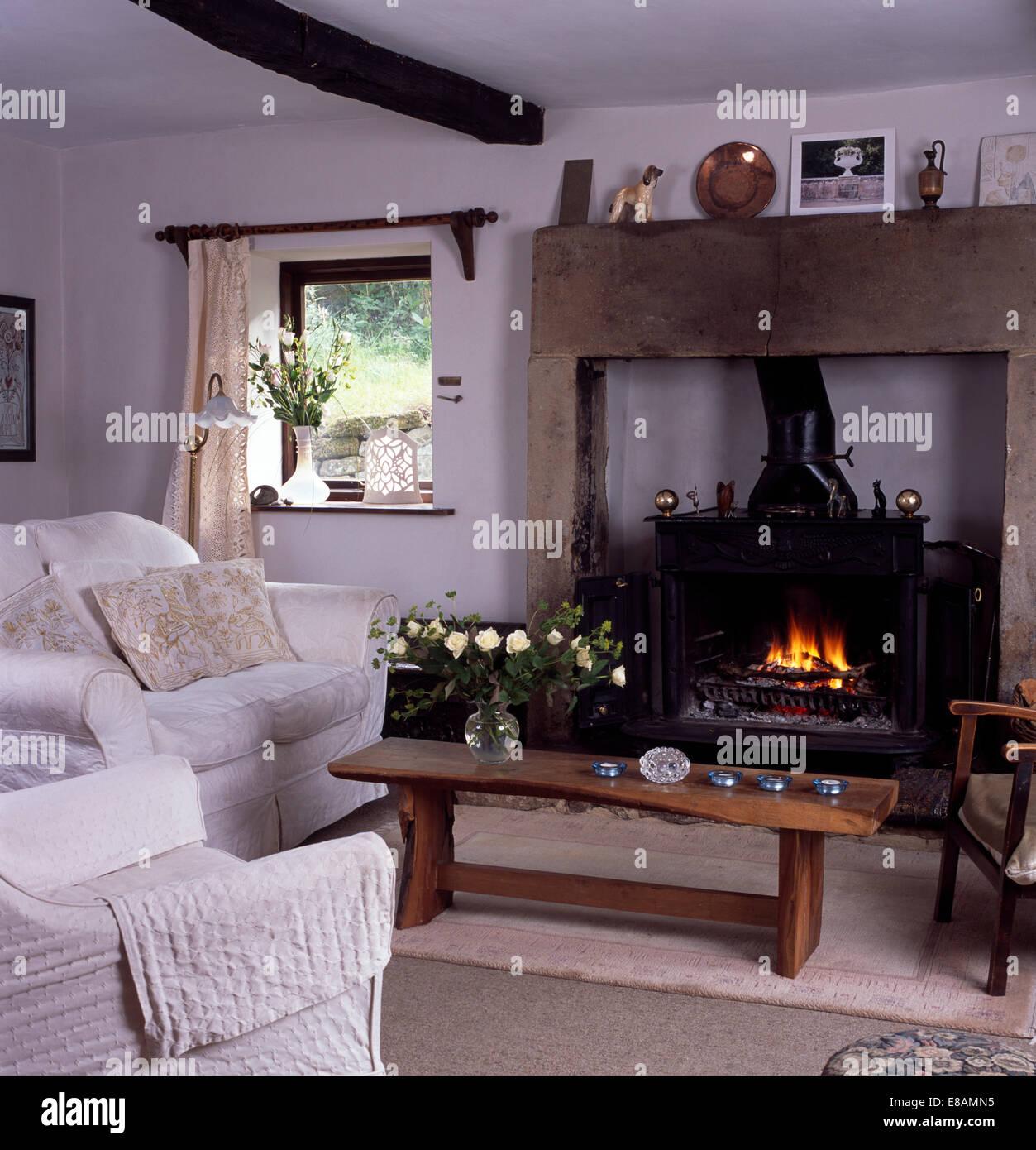 Weißes Sofa und Sessel neben einfachen Holz Couchtisch vor ...