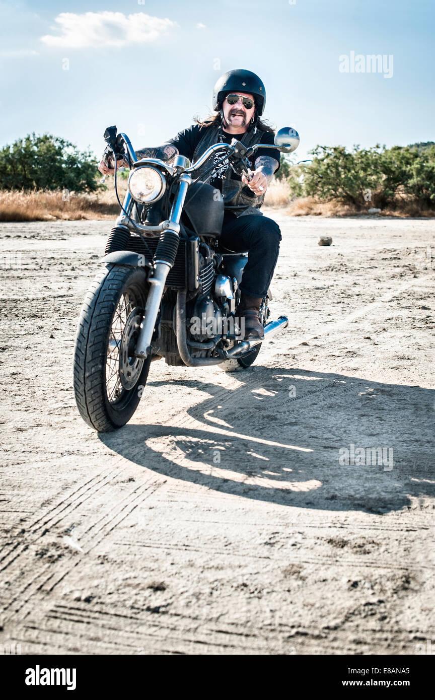 Reifer Mann Motorradfahren über trockenen Ebene, Cagliari, Sardinien, Italien Stockbild