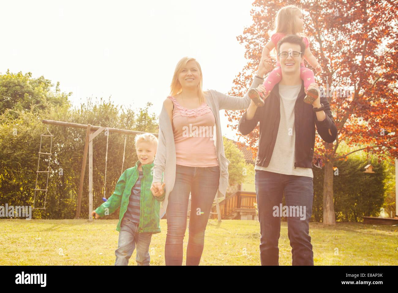 Familie im Garten, Schaukeln im Hintergrund Stockbild