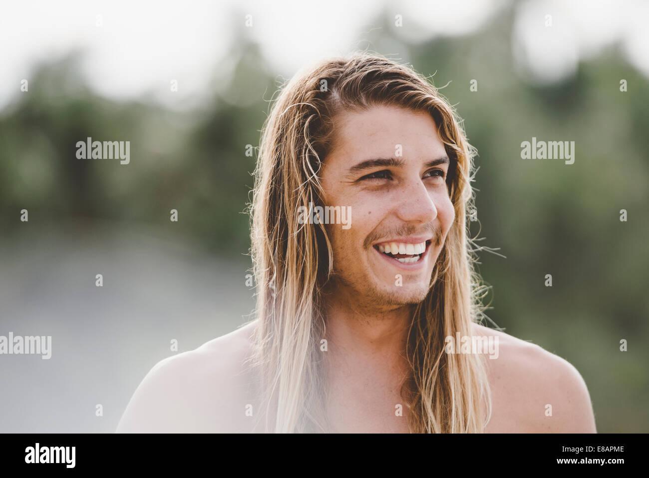 Mann in langen Haaren mit breiten Lächeln Stockbild