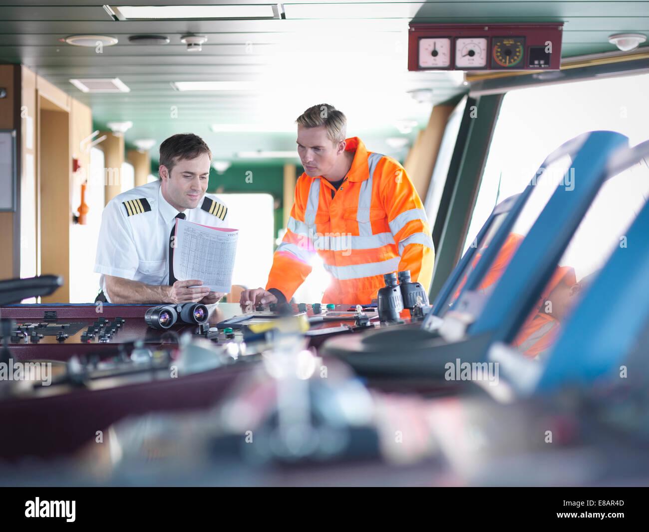 Kapitän und Arbeiter diskutieren Hinweise auf Schiffs-Brücke Stockbild