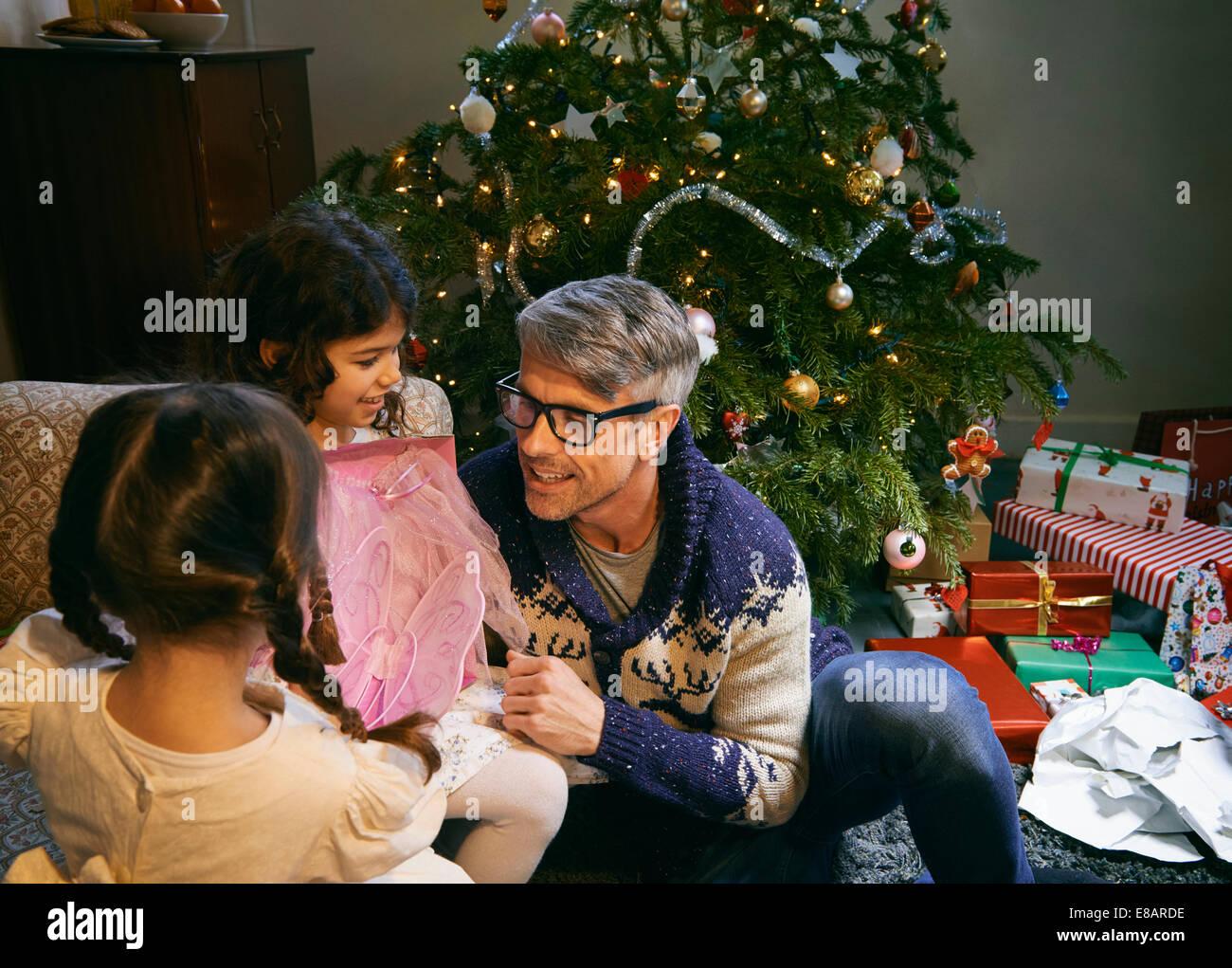 Vater und zwei Töchter, die Weihnachtsgeschenke im Wohnzimmer öffnen ...