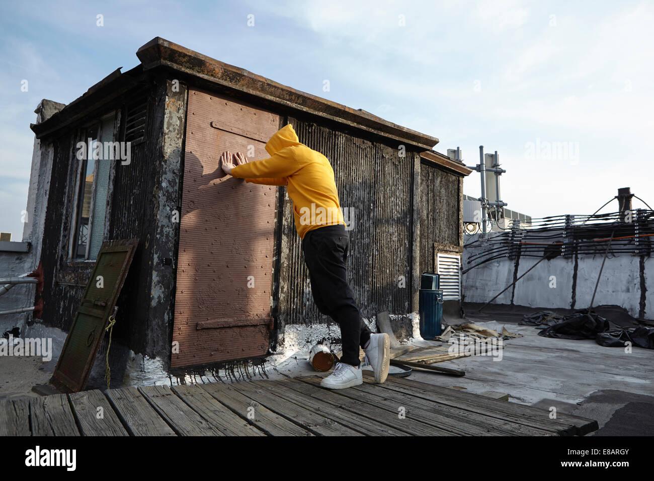 Junger Mann auf dem Dach Hütte gelehnt und blickte Stockbild