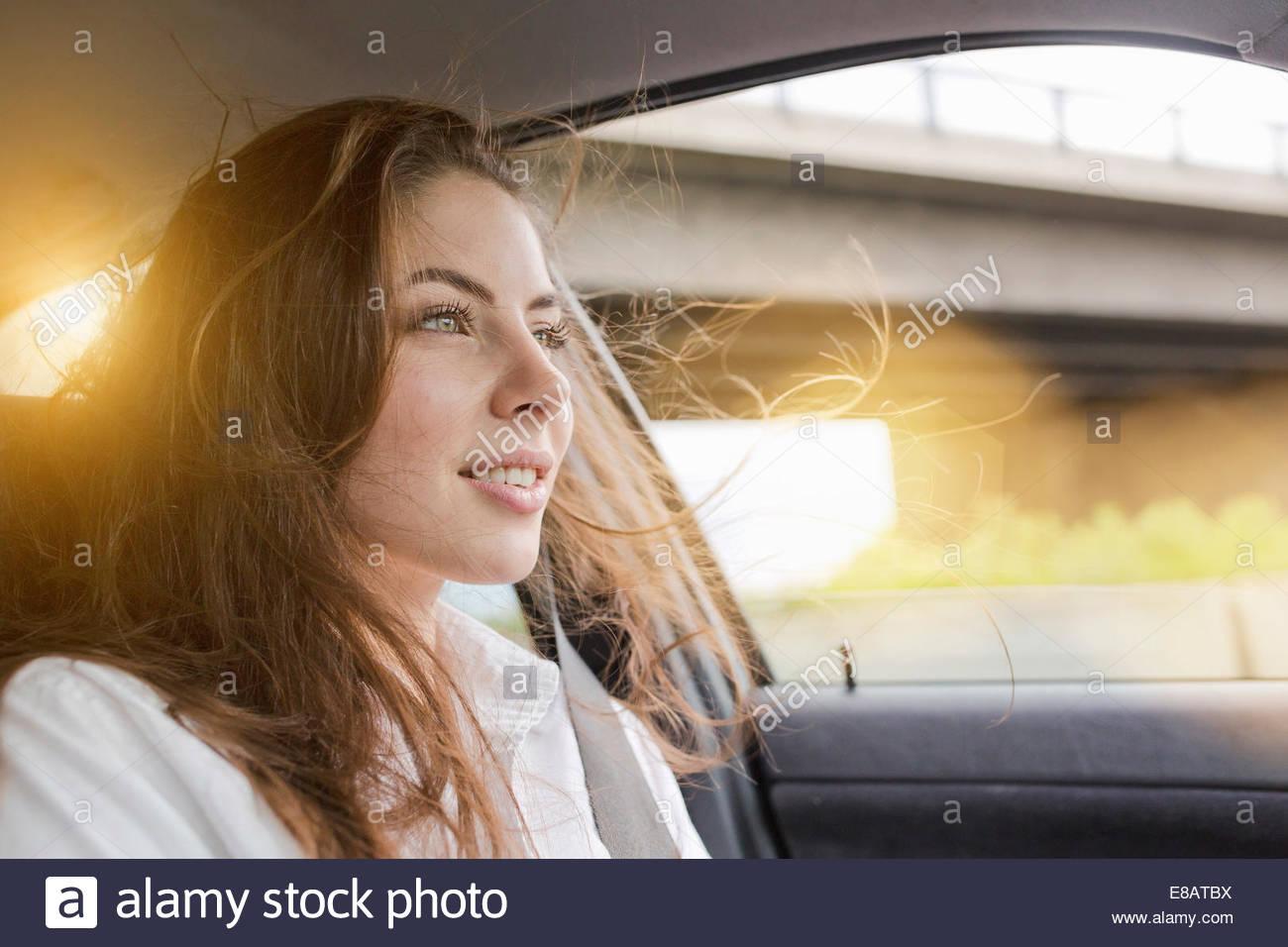 Junge Frau im Auto, Haare im Wind wehen Stockbild
