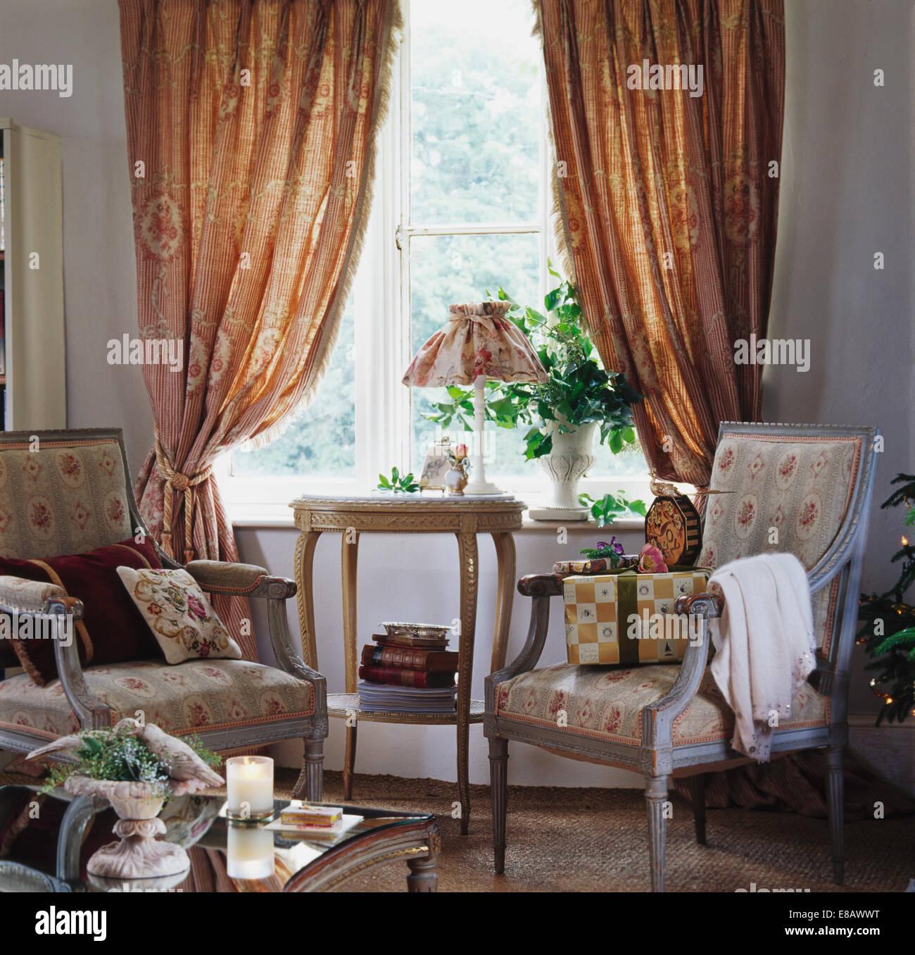 Floral Sessel vor Fenster mit gemusterten schwere Beige Vorhänge im ...