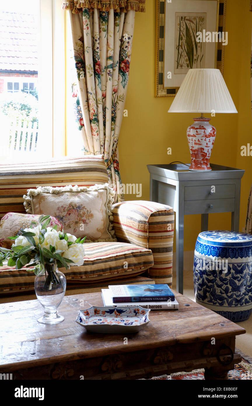 Gestreiften Sofa Und Rustikaler Couchtisch Aus Holz Im Wohnzimmer Gelb Land  Mit Einem Hohen Blaue + Weiße Chinesischen Jar