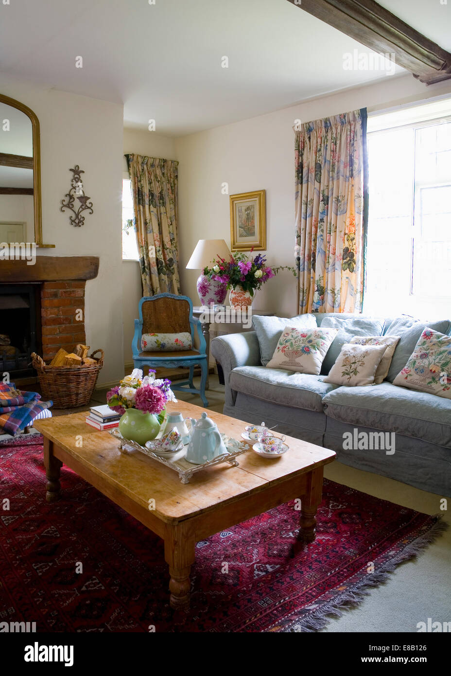 Blaues Sofa vor Fenster mit floral Gardinen im Land