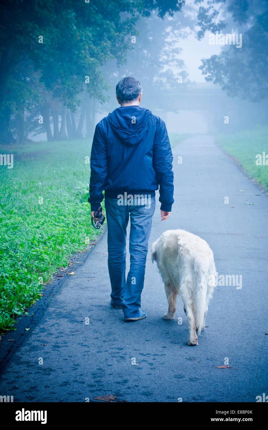 Mann geht mit seinem Hund in der Natur Stockbild